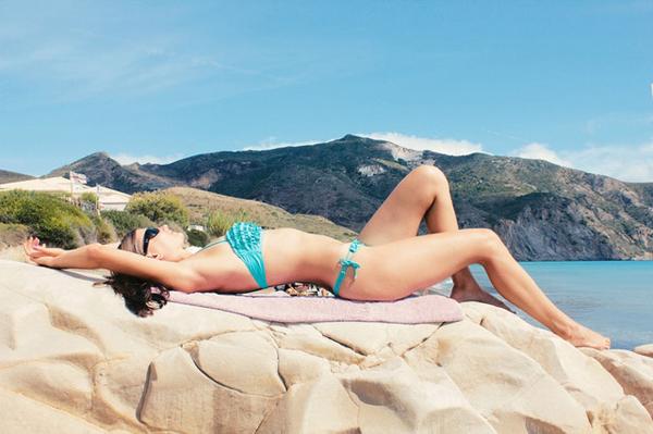 岩場に寝転ぶ女性