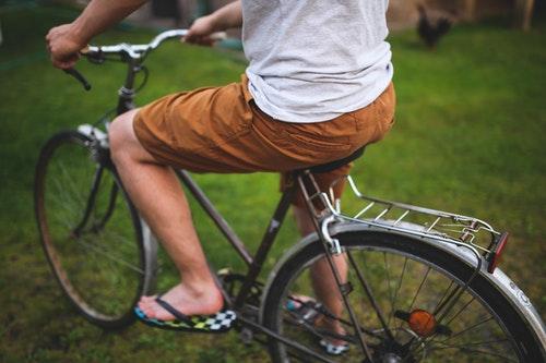 ショートパンツで自転車をこぐ男性